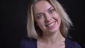 Empresaria rubia de mediana edad feliz en relojes azules de la blusa con sonrisa coqueta en cámara en fondo negro almacen de metraje de vídeo