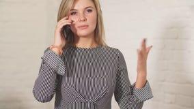 Empresaria rubia en ropa casual que habla en el teléfono celular almacen de metraje de vídeo
