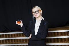 Empresaria rubia hermosa con cinta métrica en la oficina del desván en vidrios anaranjados y traje negro Concepto del asunto Foto de archivo