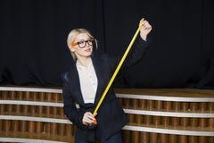 Empresaria rubia hermosa con cinta métrica en la oficina del desván en vidrios anaranjados y traje negro Concepto del asunto Foto de archivo libre de regalías