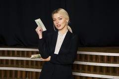 Empresaria rubia hermosa con el dinero en la oficina del desván en traje negro Imagen de archivo libre de regalías