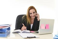 Empresaria rubia hermosa que habla en notas sonrientes de la escritura de la pluma de tenencia del teléfono móvil sobre la libret Fotos de archivo