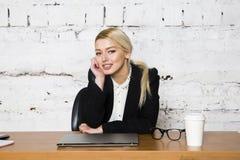 Empresaria rubia joven de la belleza que se sienta en una tabla de la oficina con el ordenador portátil, el cuaderno y los vidrio Imagen de archivo libre de regalías