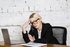 Empresaria rubia joven de la belleza que se sienta en una tabla de la oficina con el ordenador portátil, el cuaderno y los vidrio Fotos de archivo