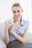 Empresaria rubia pacífica que sostiene una taza que se sienta en el sofá Fotos de archivo
