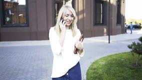 Empresaria rubia que camina en una calle del verano y que habla en su teléfono metrajes