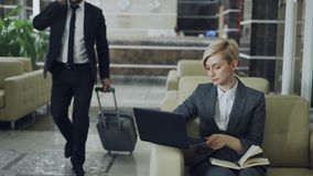 Empresaria rubia que se sienta en butaca con la libreta y el ordenador portátil mientras que hombre de negocios con equipaje que