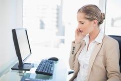 Empresaria rubia seria que tiene una presentación de la llamada de teléfono Foto de archivo libre de regalías