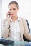 Empresaria rubia severa que tiene una presentación de la llamada de teléfono Imágenes de archivo libres de regalías