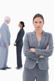 Empresaria seria con los brazos doblados y los colegas detrás de ella Fotos de archivo