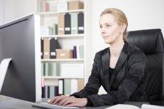 Empresaria seria en el escritorio que mecanografía en el ordenador Imagen de archivo