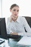 Empresaria seria que se sienta en su escritorio Imagen de archivo