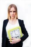Empresaria seria que sostiene el reloj grande Fotos de archivo