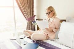 Empresaria seria que trabaja con los documentos en hotel imagen de archivo
