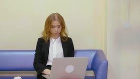 Empresaria seria que trabaja en el ordenador portátil mientras que se sienta en el sofá en oficina almacen de video