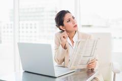 Empresaria severa que sostiene el periódico mientras que trabaja en lo del ordenador portátil Fotos de archivo
