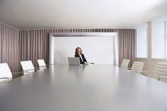 Empresaria Sitting In Boardroom con el ordenador portátil Imágenes de archivo libres de regalías