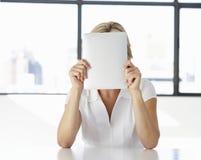 Empresaria Sitting At Desk en oficina con la cara ocultada detrás de la tableta de Digitaces Imagen de archivo libre de regalías