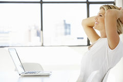 Empresaria Sitting At Desk en oficina usando el ordenador portátil Imagen de archivo