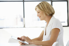 Empresaria Sitting At Desk en oficina usando la tableta de Digitaces Fotografía de archivo