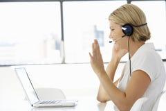 Empresaria Sitting At Desk en oficina usando las auriculares que llevan del ordenador portátil Fotografía de archivo