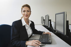 Empresaria Sitting At Row de ordenadores Fotografía de archivo