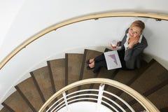 Empresaria Sitting On Stairs en el teléfono móvil Fotografía de archivo libre de regalías