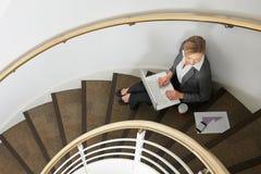 Empresaria Sitting On Stairs que usa el ordenador portátil Imagen de archivo libre de regalías