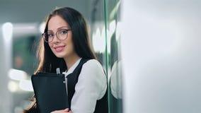 Empresaria sonriente acertada atractiva del retrato en los vidrios que se colocan en pasillo metrajes