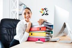 Empresaria sonriente alegre que pone en la pila de carpetas coloridas Imagen de archivo libre de regalías
