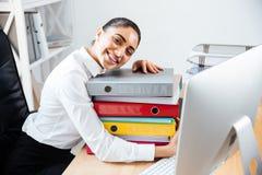 Empresaria sonriente alegre que pone en la pila de carpetas coloridas Fotografía de archivo