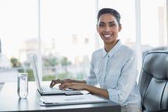 Empresaria sonriente alegre que trabaja en su ordenador portátil Imagenes de archivo