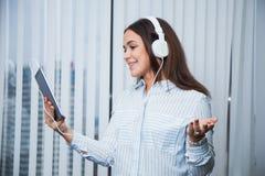 Empresaria sonriente bonita en los auriculares blancos que sostienen la tableta digital imágenes de archivo libres de regalías