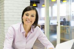 Empresaria sonriente bonita que trabaja en la oficina, lo Imagen de archivo