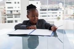 Empresaria sonriente con el fichero y pluma que se sienta en la mesa de reuniones Fotos de archivo