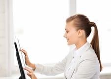 Empresaria sonriente con la pantalla táctil en oficina Foto de archivo libre de regalías