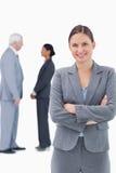 Empresaria sonriente con los brazos doblados y colegas detrás de ella Fotografía de archivo