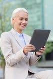 Empresaria sonriente con PC de la tableta al aire libre Fotografía de archivo