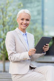 Empresaria sonriente con PC de la tableta al aire libre Imagen de archivo