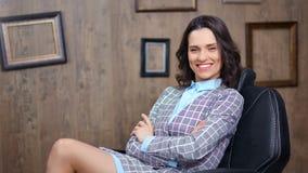 Empresaria sonriente confiada que se sienta en silla del CEO con las manos cruzadas que miran la cámara almacen de metraje de vídeo