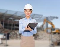 Empresaria sonriente en casco con el tablero Fotografía de archivo