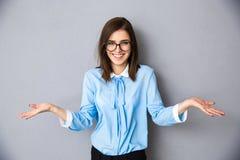 Empresaria sonriente en el gesto de pedir sobre fondo gris Imagen de archivo libre de regalías