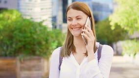 Empresaria sonriente en la camisa blanca que se coloca en dictrict céntrico del negocio que habla en smartphone metrajes