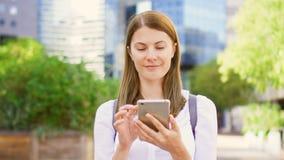Empresaria sonriente en la camisa blanca que se coloca en distrito financiero céntrico usando smartphone almacen de video
