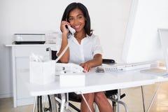 Empresaria sonriente en la silla de ruedas que trabaja en su escritorio Fotos de archivo libres de regalías
