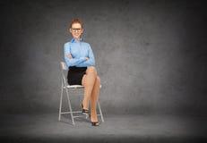 Empresaria sonriente en los vidrios que se sientan en silla Imágenes de archivo libres de regalías