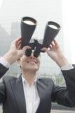 Empresaria sonriente en un traje que mira para arriba a través de los prismáticos al aire libre en Pekín Imagenes de archivo