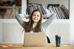 Empresaria sonriente feliz que se relaja en el escritorio del trabajo en offi moderno Fotografía de archivo libre de regalías