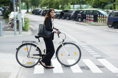 Empresaria sonriente With Handbag Commuting en la bicicleta Fotografía de archivo
