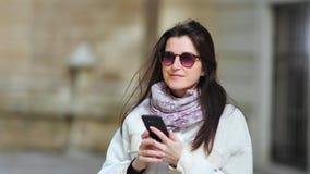 Empresaria sonriente hermosa que disfruta de la rotura usando el smartphone al aire libre en el primer medio del día soleado almacen de video